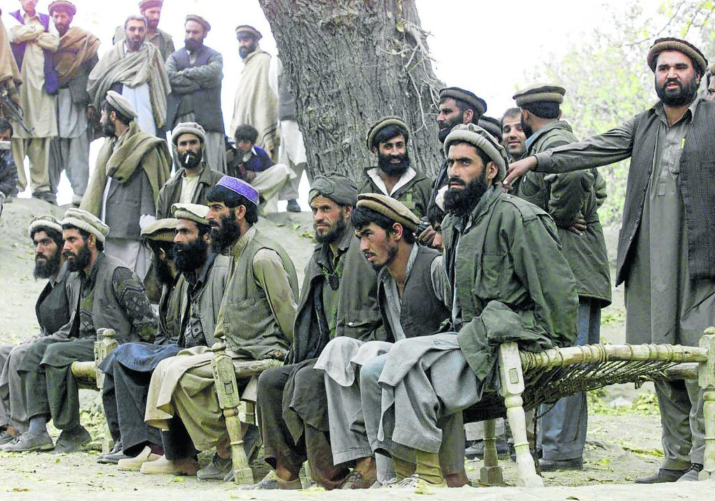 "Captured Afghan al Qaeda members sit on a bench as they are presented to the media in Tora Bora, in this file picture taken December 17, 2001. Al Qaeda leader Osama bin Laden was killed May 1, 2011 in a firefight with U.S. forces in Pakistan and his body was recovered, President Barack Obama said on Sunday. ""Justice has been done,"" Obama said in a dramatic, late-night White House speech announcing the death of the elusive mastermind of the Sept. 11, 2001, attacks on New York and Washington that killed nearly 3,000 people. Bin Laden had been hunted since he eluded U.S. soldiers and Afghan militia forces in a large-scale assault on the Tora Bora mountains of Afghanistan close to the Pakistan frontier in 2001.                       REUTERS/Erik de Castro   (AFGHANISTAN - Tags: CIVIL UNREST)"