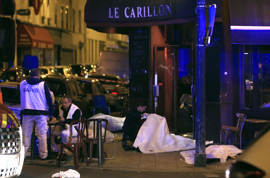 Victims lay on the pavement in a Paris restaurant, Friday, Nov. 13, 2015. Police officials in France on Friday reported a shootout in a Paris restaurant and an explosion in a bar near a Paris stadium. It was unclear if the events were linked.