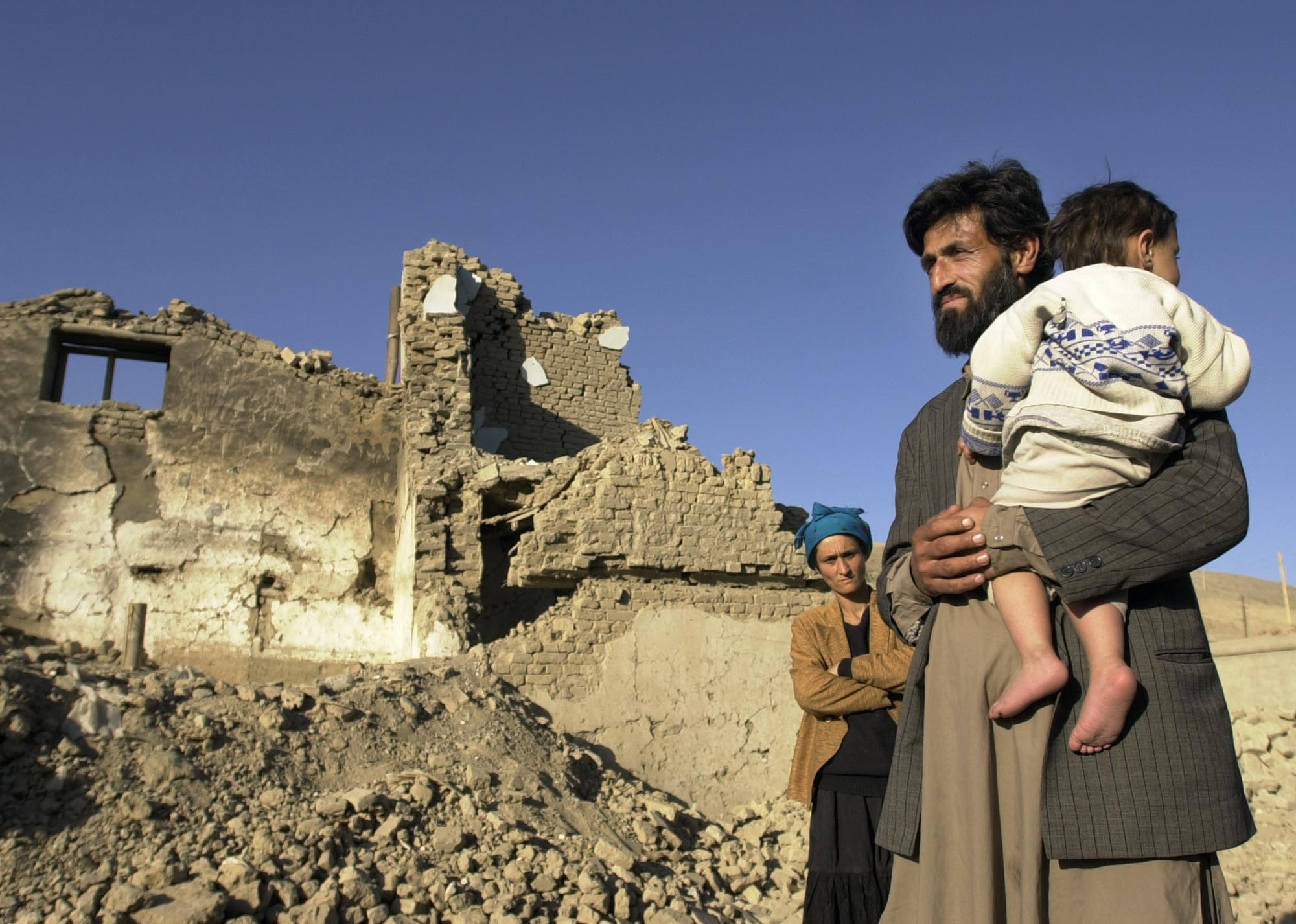 ORG XMIT: NY925 FILE - In this Tuesday, Nov. 20, 2001 file photo, Mohammed Sulemon stands with his wife Rona and their daughter Kanite in front of their home in Kabul, Afghanistan, which was bombed in the U.S. attacks. The family, which moved to a room in the back of the damaged house, says the bomb was intended for a Taliban military target near their home. No one was injured in this bombing. (AP Photo/Laura Rauch)