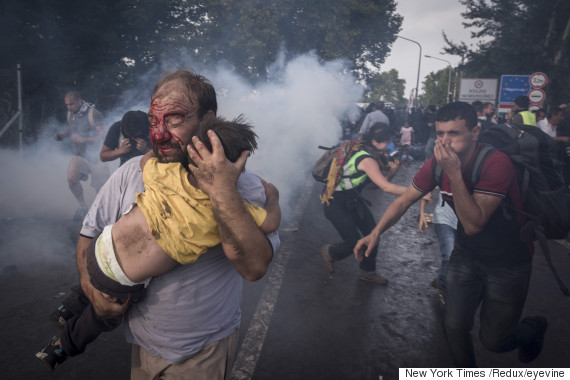 A migrant holds his child during a clash with Hungarian riot police at the Horgos border crossing in Serbia, Sept. 16, 2015. Hundreds of migrants remained stranded on Serbia's border with Hungary early Wednesday as Hungary's decision to seal its border rippled across Europe and other migrants scrambled to find alternative routes, in an effort, in most cases, to reach Germany. (Sergey Ponomarev/The New York Times) Credit: New York Times / Redux / eyevine For further information please contact eyevine tel: +44 (0) 20 8709 8709 e-mail: info@eyevine.com www.eyevine.com