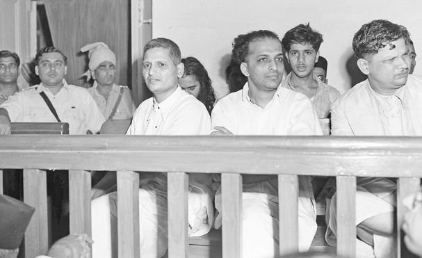 The men accused of the assassination of Mahatma Gandhi listen to testimony in a courtroom during their arraignment in New Delhi, India, on May 27, 1948. Gandhi was shot three times by Nathuram Vinayak Godse, center, on his way to a prayer meeting from Birla House on Jan. 30. At left is Narayan Dattraya Apte and at right is Vishnu Ramkrishna Karkare. In second row at center is Madan Lal, accused of exploding a bomb on Jan. 20 outside a Gandhi prayer meeting at Birla House. Men at doorway are unidentified. (AP Photo/Max Desfor)