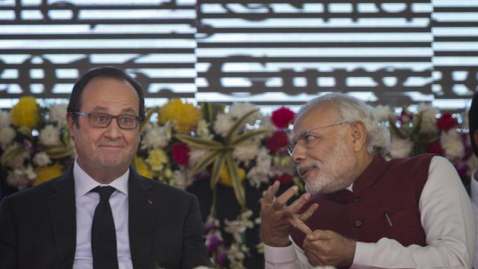 French President Francois Hollande, left, and Indian Prime Minister Narendra Modi interact during the foundation stone laying for the headquarters of the International Solar Alliance at Gurgaon, outskirts of New Delhi, India, Monday, Jan. 25, 2016. The solar energy alliance was launched last month during global climate talks held in Paris. Hollande is on a three-day visit to India.(AP Photo/Saurabh Das)