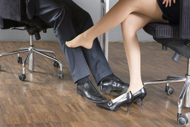 Woman stroking businessman's leg with her foot